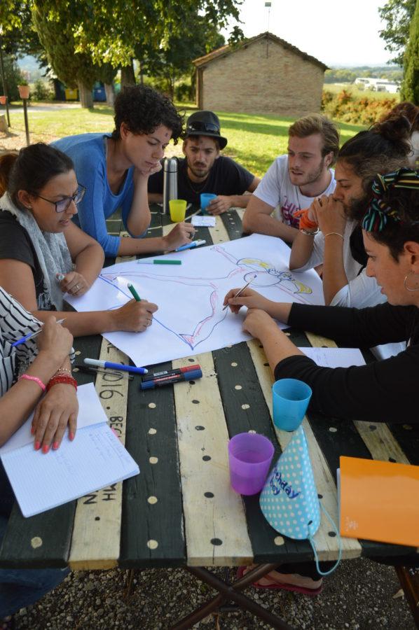 partecipanti lavorano attorno ad un tavolo